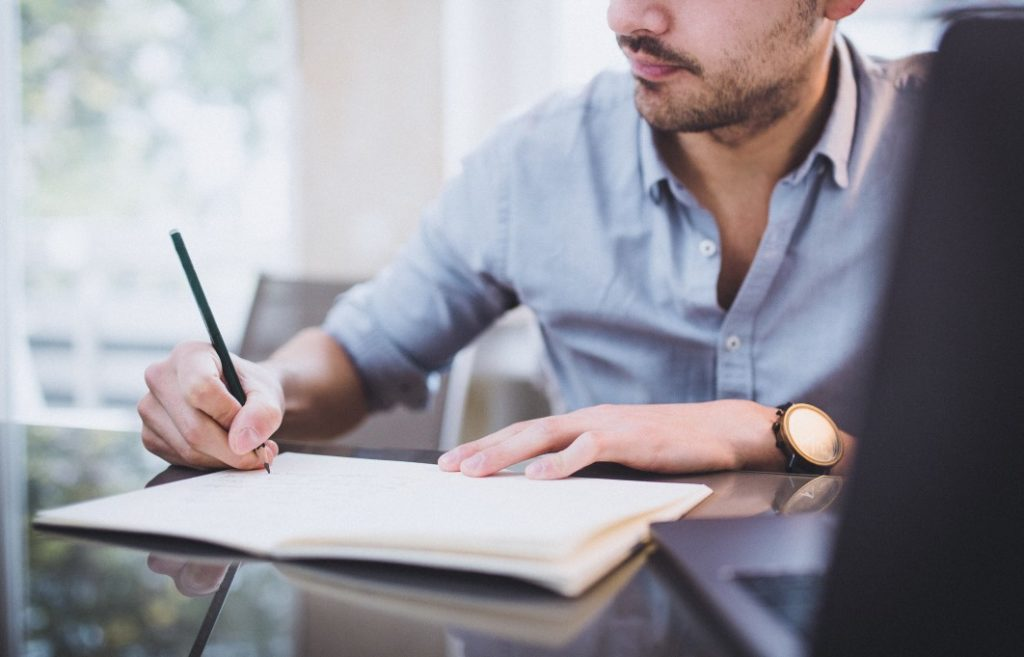 Man writing in notebook, brainstorming scholarship fund