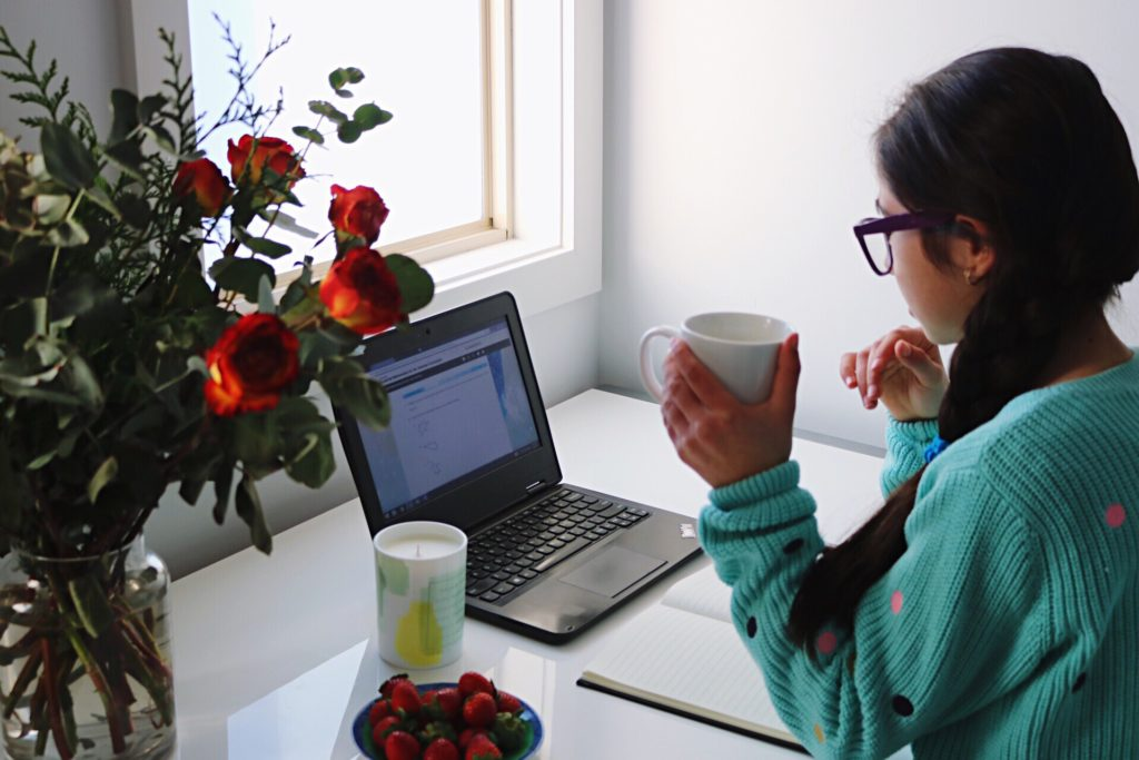 Student sitting at desk with flowers and coffee