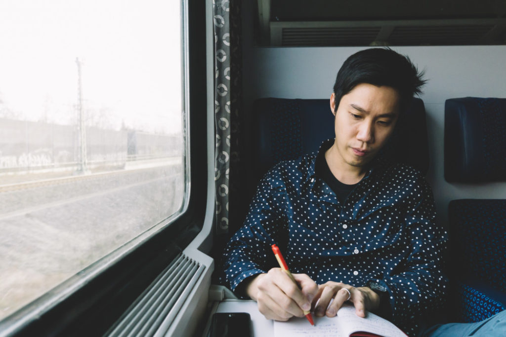 Student on the train, writing in notebook